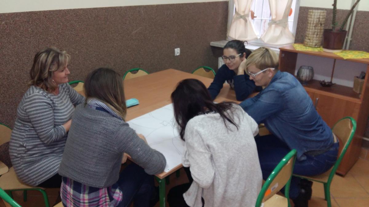 Kobieta z dziećmi podczas zajęć przy stole