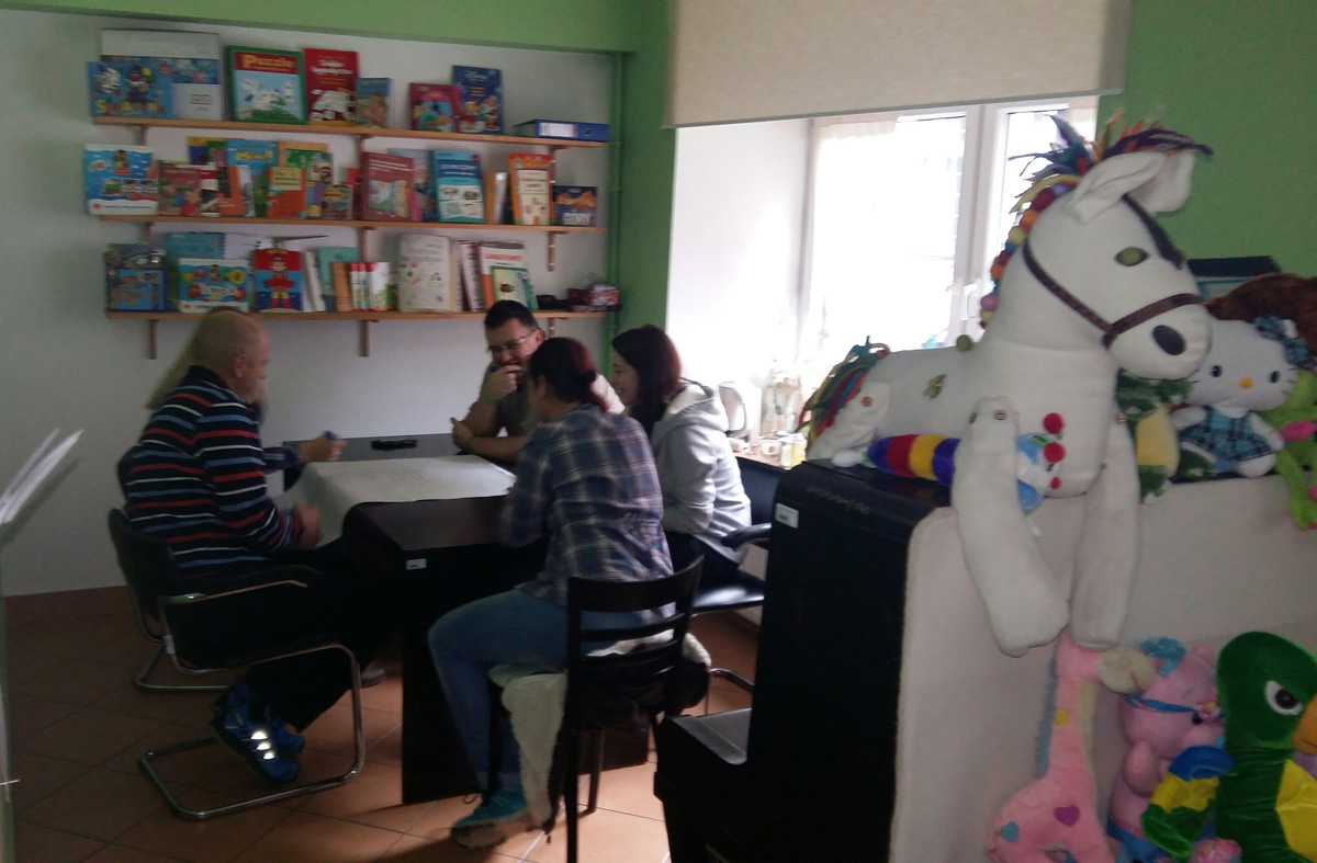 Kobieta z dziećmi podczas zajęć w pokoju