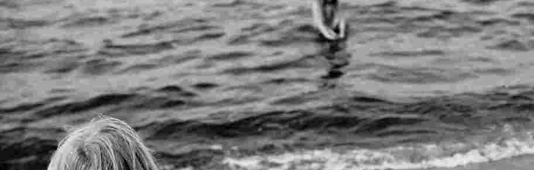 Dziecko na plaży i jedna osoba w wodzie